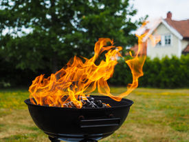 stock photo of hughes  - Hugh flame on a grill with charcoal on green lawn - JPG