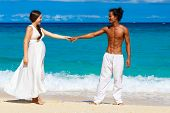 Happy And Young Pregnant Couple Having Fun On A Tropical Beach. Summer Vacation.