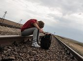 Teen girl with problems sitting on rail road