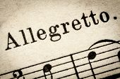 allegretto -  fast, quickly and bright music tempo (close to but not quite allegro) - macro detail from vintage sheet music