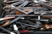 stock photo of shotgun  - rubbish container with broken shotguns rifles and other old weapon - JPG