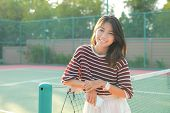 stock photo of short skirt  - portrait of beautiful young asian woman wearing white clothes skirt in tennis course with happy face - JPG