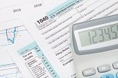 image of cpa  - Calculator over US 1040 Tax Form - studio shot