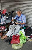 BANGKOK, THAILAND - DECEMBER 25, 2014: Street Photography of shoemaker repairing old shoes.
