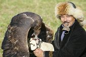 Man feeds golden eagle, circa Almaty, Kazakhstan.