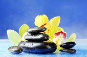 Spa stones with steam and beautiful blooming orchid on blue background