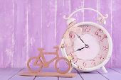 Beautiful vintage alarm clock with decorative bicycle on table on wooden background