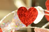 Single flat shiny red foil heart on silver string close up