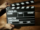 Movie clapper in female hand on wooden background