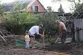Family Planting Seedling In Garden
