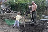 Grandfather With Grandson Planting Seedling
