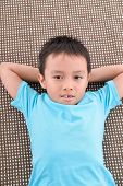little boy in blue dress lying on in bed