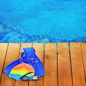 Bright beach accessories on pool background