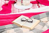 Book and glasses on bed close-up