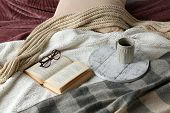 Book, glasses and cup of tea on bed close-up