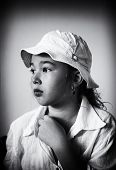 Black and white portrait of a pensive little girl in a white panama