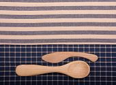 Wooden knife and spoon on off white and blue kitchen towels