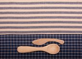 Wooden spoon and knife on blue and off white linen kitchen towels