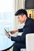 Businessman in Asian hotel room working with tablet