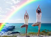 fitness, sport, people, yoga and lifestyle concept - happy couple meditating in tree pose on summer beach from back