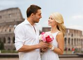 summer holidays, travel, tourism, people and dating concept - happy couple with bunch of flowers over coliseum background