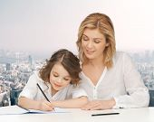 people, family, school, home education and parenting concept -happy mother and daughter doing homework and writing in notebook over city background