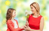 people, holidays, relations and family concept - happy little daughter giving flowers to her mother over green lights background