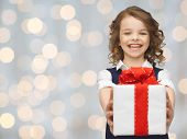 people, childhood, summer and holidays concept - happy smiling girl with gift box over lights background