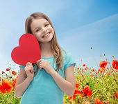 love, charity, holidays, children and people concept - smiling little girl with red heart over blue sky and poppy field background