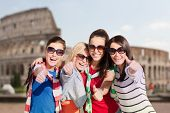 summer holidays, vacation, travel, friendship and people concept - happy teenage girls or young women in sunglasses showing thumbs up and laughing over coliseum background