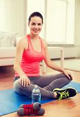fitness, home and diet concept - smiling teenage girl with bottle of water and dumbbells after exercising at home