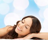 beauty, people and health concept - beautiful young woman lying with closed eyes over blue lights background