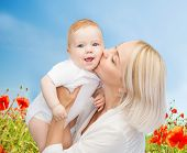 people, family, motherhood and children concept - happy mother hugging adorable baby over blue sky and poppy field background