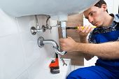 Plumber Fixing Sink In Bathroom