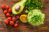 Guacamole On Wooden Table Surrounded By Its Ingridients