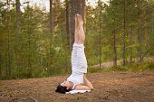 Young Woman In Yoga Shoulder Stand In Forest