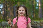 Little Girl Pick Up Mushrooms In The Forest