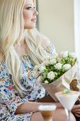 Young woman with a bouquet of white roses at the cafe table.