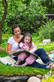 Mother And Daughter Read Book Outdoors
