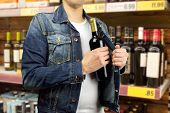 foto of stealing  - man in a supermarket stealing a bottle of champagne - JPG