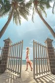 Young beautiful woman walking on the sunny tropical