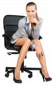 Businesswoman on office chair with head reclined upon her hand