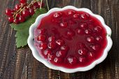 Red Currant Jam In A White Platter And A Sprig Of Currant With Berries On The Table.