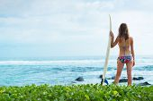 Young lady surfer standing on the beach with surf board