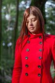 pic of overcoats  - Young woman feeling sad walking on a forest wearing a red overcoat during winter under a sunlight ray - JPG