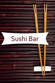 Pair of chopsticks and Sushi Bar text on bamboo mat background