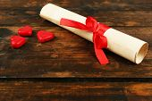 Rolled paper with hearts on rustic wooden table background
