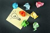 Symbol of idea as light bulb on sheet of paper with crumpled paper on color table background