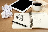 Symbol of idea as light bulb in notebook with crumpled paper, tablet and cup of coffee on wooden desk background