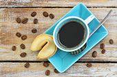 Coffee with fortune cookie on rustic wooden surface